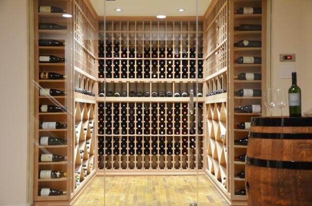 Custom Home Wine cellar with an Efficient Cooling unit, Elegant Wood Wine Racks, and Contemporary Glass Doors
